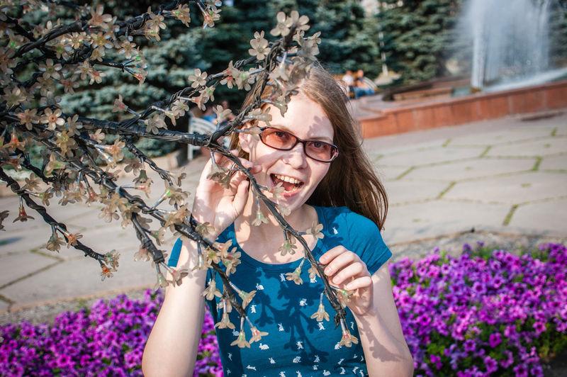 Portrait of teenage girl by fairy lights on tree