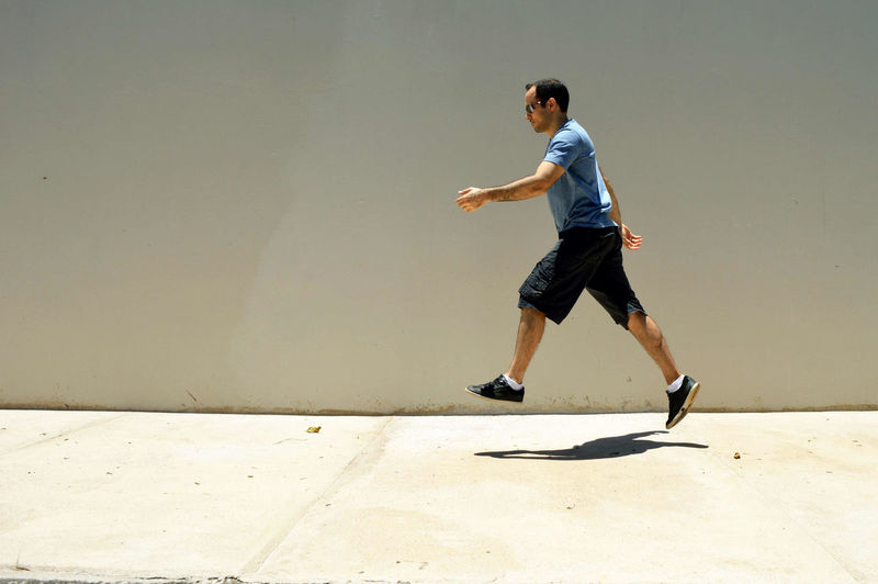 Side View Of Man Levitating Over Sidewalk By Wall