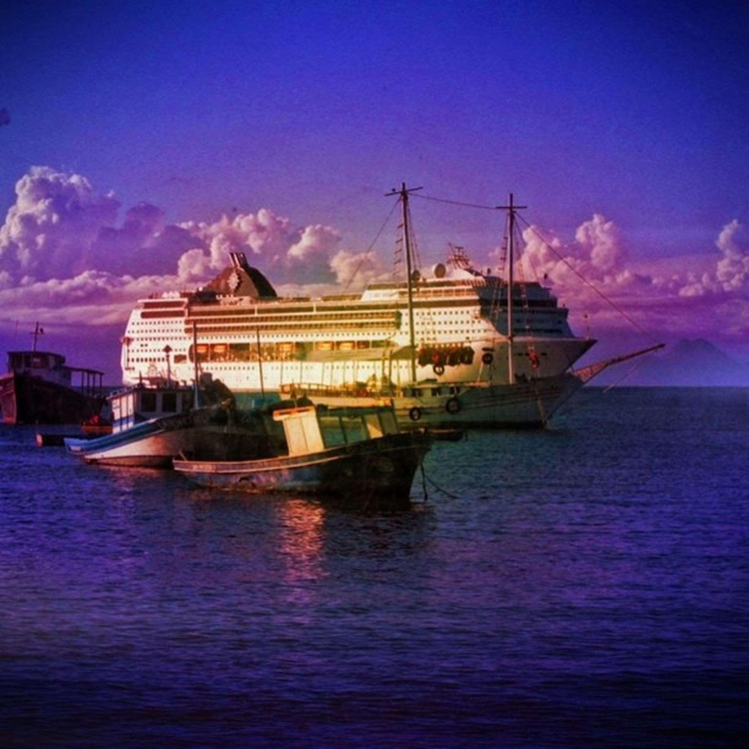 water, waterfront, sky, nautical vessel, sea, boat, transportation, mode of transport, cloud - sky, moored, blue, sunset, built structure, building exterior, cloud, rippled, architecture, nature, reflection, beauty in nature