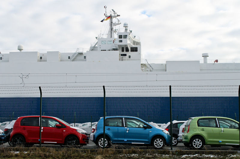 Cars parked at parking lot by ship