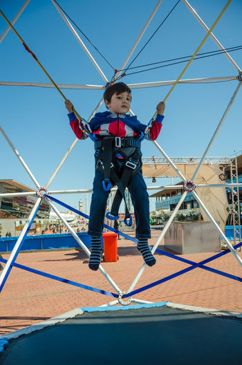 A young boy bounces on a trampoline while attached to bungie ropes. Blue Sky BOUNCE Bouncing Boy Bungie Child Childhood Clear Sky Day Energetic Exercise Fun Happiness Happy Jump Jumping Lifestyles One Person Outdoors Outside Sky Sport Trampoline Young