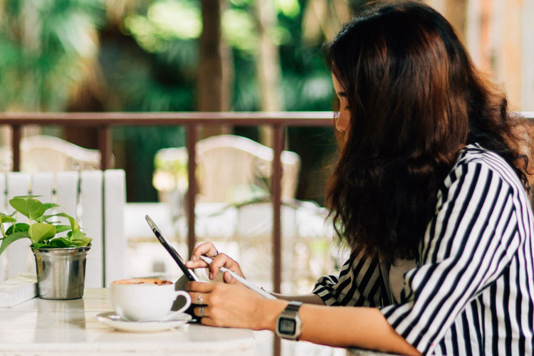 Woman using digital tablet while having coffee at table in cafe