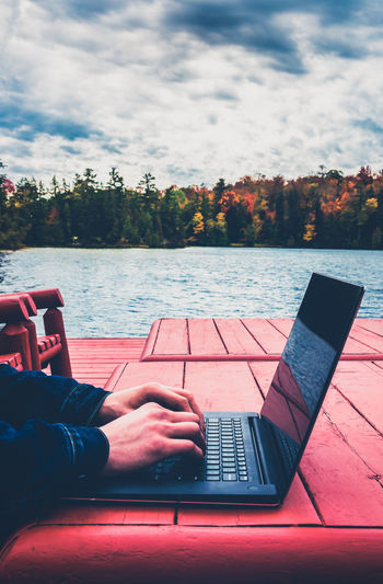 A freelance male taking outdoors in autumn, laptop by the lake. blurred bkgrd - aged effect filtered