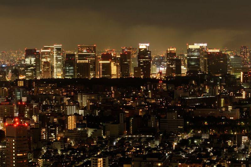 Illuminated cityscape against sky night