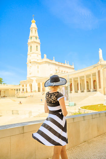 Rear view of woman looking at church against blue sky