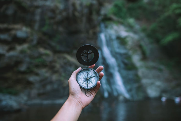 Cropped hand of person holding navigational compass against waterfall