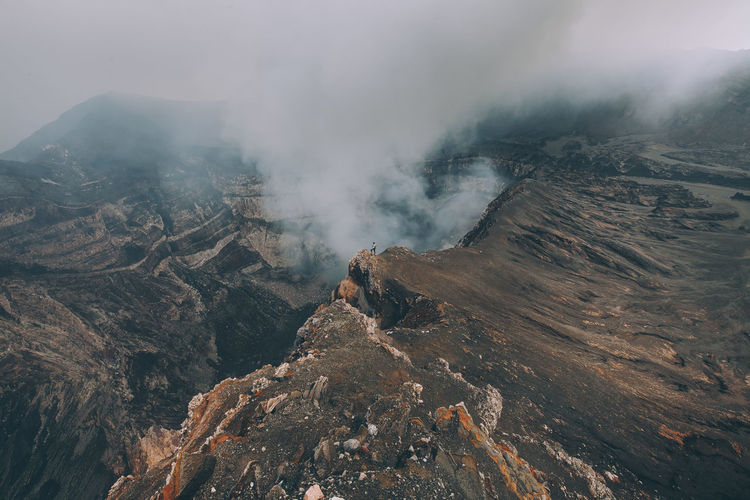 High angle view of woman standing by smoke emitting from volcanic crater