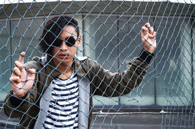 Portrait of young man looking through chainlink fence