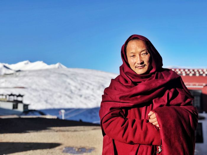 Portrait of monk standing against snowcapped mountain