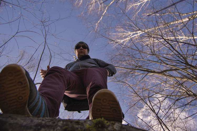 Low angle view of man sitting by bare tree against sky
