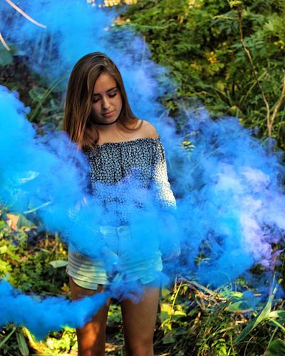 Young woman standing by smoke against plants