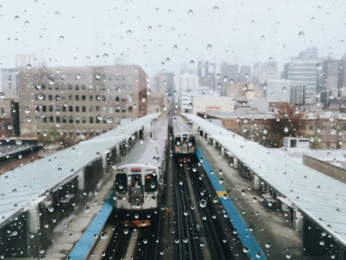 High angle view of trains at railroad station seen through glass window during rainy season
