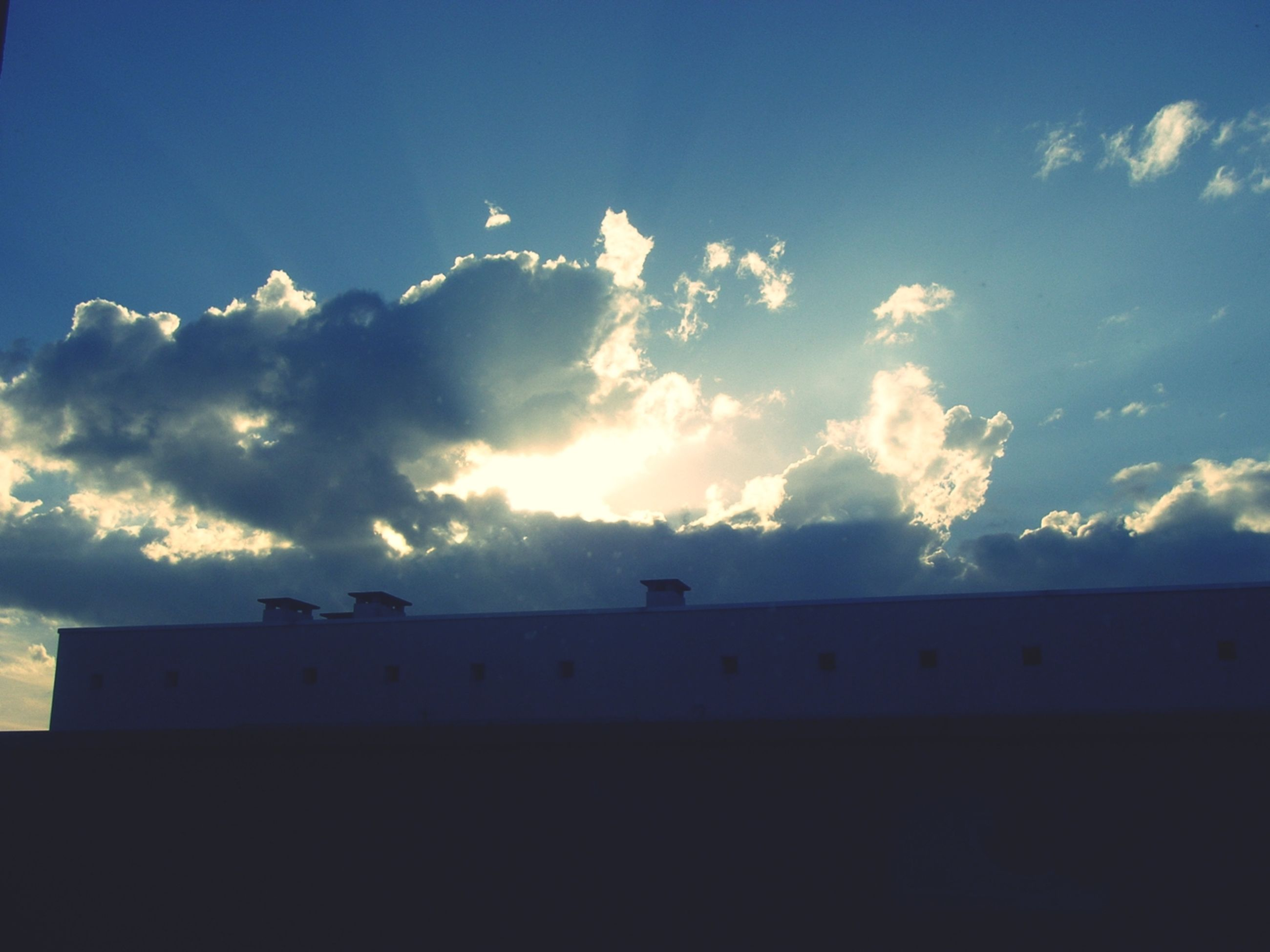 sky, silhouette, sunset, cloud - sky, blue, cloud, built structure, beauty in nature, scenics, sunlight, nature, building exterior, copy space, tranquility, tranquil scene, architecture, low angle view, house, sun, outdoors