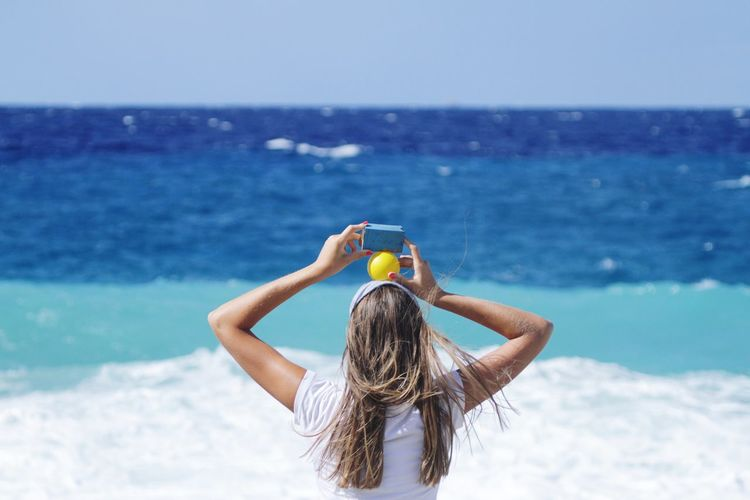 Rear view of woman holding toys on beach against clear sky