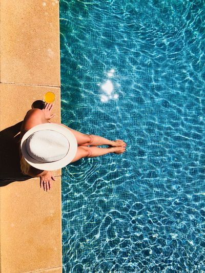 High angle view of woman wearing hat sitting at poolside during sunny day