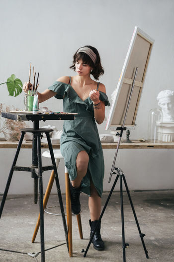 Full length of painter sitting on stool by easel at art studio