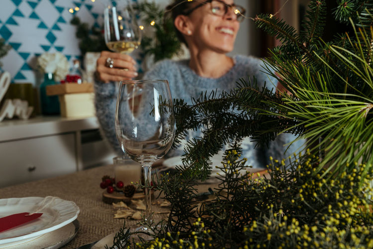 Smiling woman drinking wine sitting by christmas tree at home