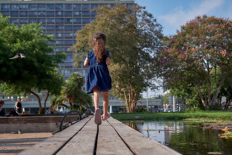 Rear view of girl running on footbridge over lake