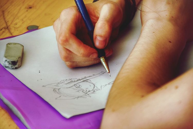 Close-up of woman making drawing on paper