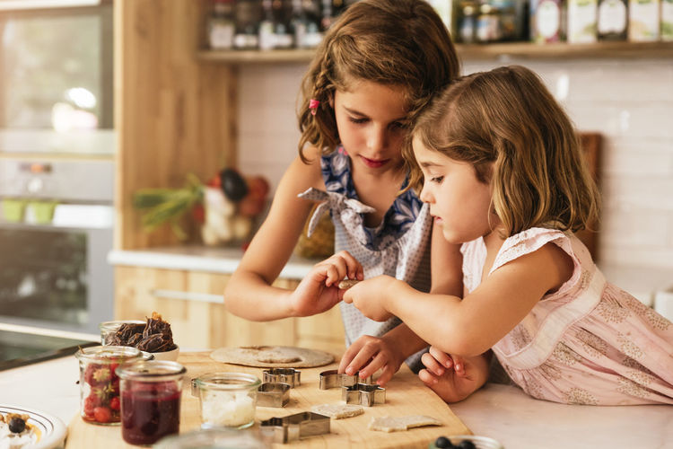 Childhood Child Togetherness Indoors  Women Girls Cooking Kitchen Chocolate Daughter Sisters Happy Family Home Copy Space People Blonde Caucasian Fun Love Food Healthy Recipe Sweet Lifestyle
