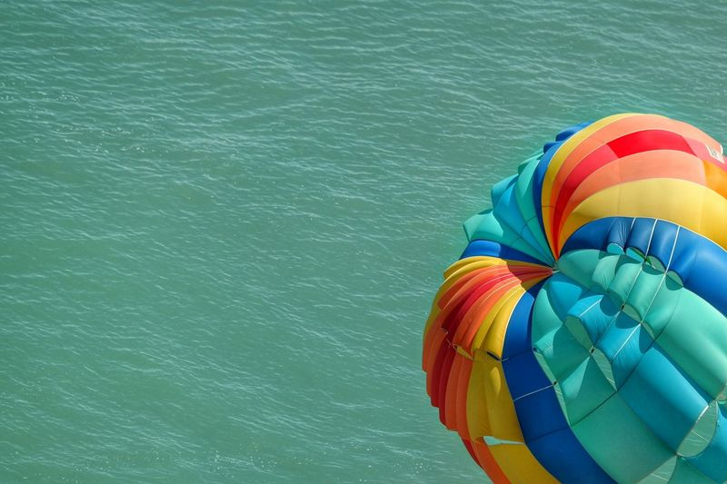 High angle view of hot air balloon flying above sea