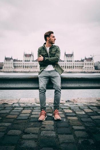 Full length of man sitting on railing in city
