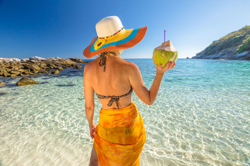 Back of happy and fashionable tourist woman with colorful sarong in turquoise water of Maya Bay famous lagoon of The Beach movie, Phi Phi Leh, Andaman Sea in Thailand Fashionable and happy tourist with sarong and pink wide-brimmed hat making a selfie on tropical famous beach of Nai Harn Beach, Rawai, Phuket, Thailand. Happy tourist enjoys panorama from Sail Rock View Point of kor 8 of Similan Islands National Park, Phang Nga, Thailand, one of the tourist attraction of the Andaman Sea. Happy woman with bikini and shorts, jumping in the air on Ya Nui Beach, a little cove divided by a rocky cape, Phuket, Thailand, Asia. Happy Koh Rok Islands Nui Beach Phang Nga Bay Phuket Thailand Tanning ☀ Thailand Vacations Woman Adult Beach Beautiful Woman Beauty Beauty In Nature Clear Sky Day Girl Hat Koh Rok Lifestyles Nature One Person One Woman Only Only Women Outdoors Phang Nga Rawai Real People Rear View Scenics Sea Seascape Sky Standing Surin Islands Travel Destinations Vacations Water Women Young Adult Young Women