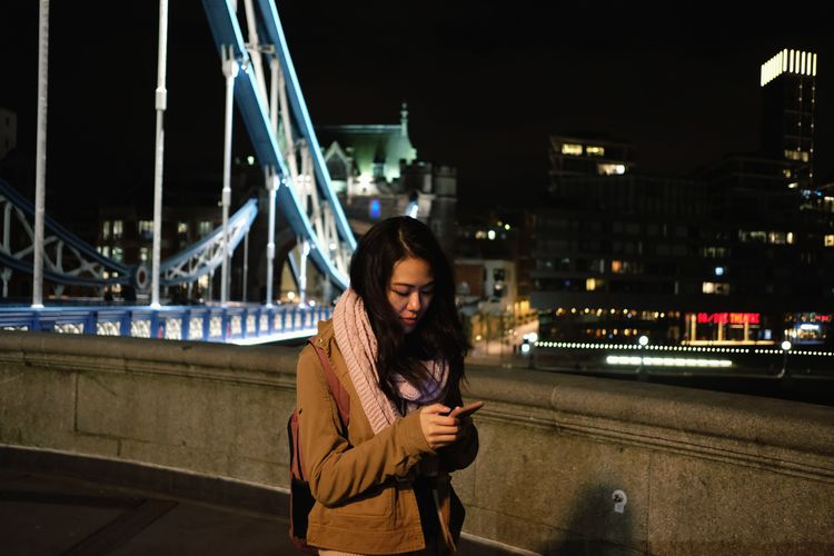 Young woman using mobile phone while standing on bridge at night