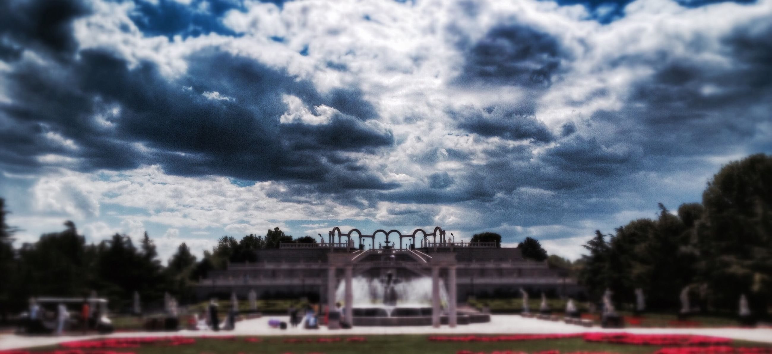 sky, cloud - sky, architecture, tree, cloudy, built structure, building exterior, cloud, overcast, weather, incidental people, travel destinations, outdoors, park - man made space, fountain, day, storm cloud, famous place, dusk, nature