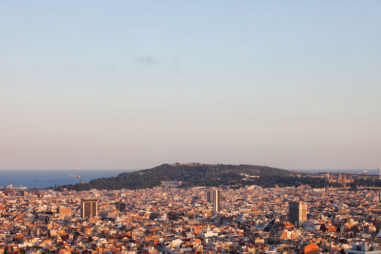 View over city of Barcelona in Catalonia, Spain at sunset in direction of Montjuic hill. Barcelona Catalonia Catalunya Houses Mediterranean  Montjuic SPAIN Aerial View Architecture Building Exterior Built Structure City City Location Cityscape Drone View Europe High Angle View Metropolis Montjuic Hill Residential Building Residential District Sundown Sunset Urban Urban Landscape