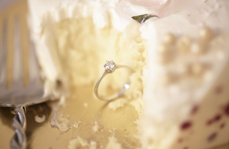 High angle view of diamond ring with wedding cake