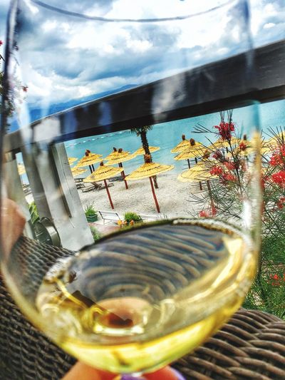 Beach umbrellas seen through wineglass