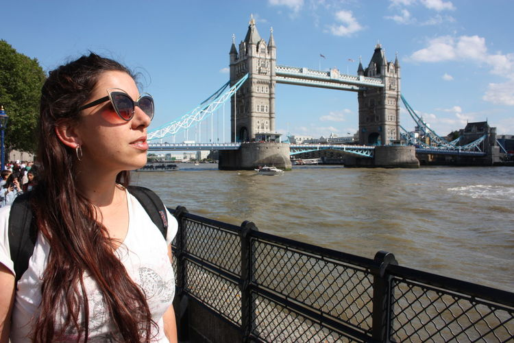 Young woman standing by railing at bridge against sky