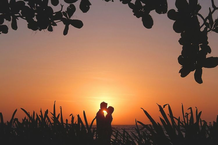 Silhouette Couple Kissing While Standing At Beach Against Orange Sky During Sunset