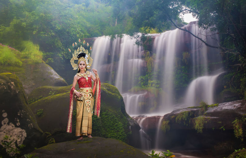 Portrait of beautiful young woman wearing crown and traditional clothing while standing against waterfall in forest