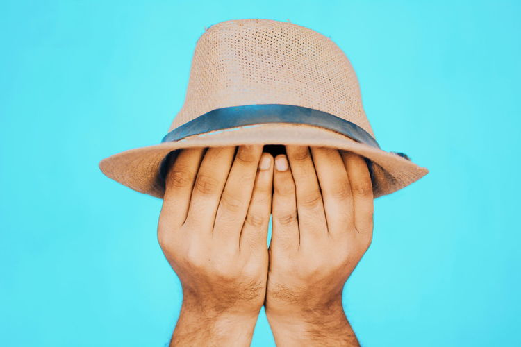 Blue Blue Background Body Part Close-up Clothing Colored Background Day Finger Hand Hat Holding Human Body Part Human Hand Indoors  Men Obscured Face One Person Real People Studio Shot Unrecognizable Person The Creative - 2018 EyeEm Awards The Still Life Photographer - 2018 EyeEm Awards