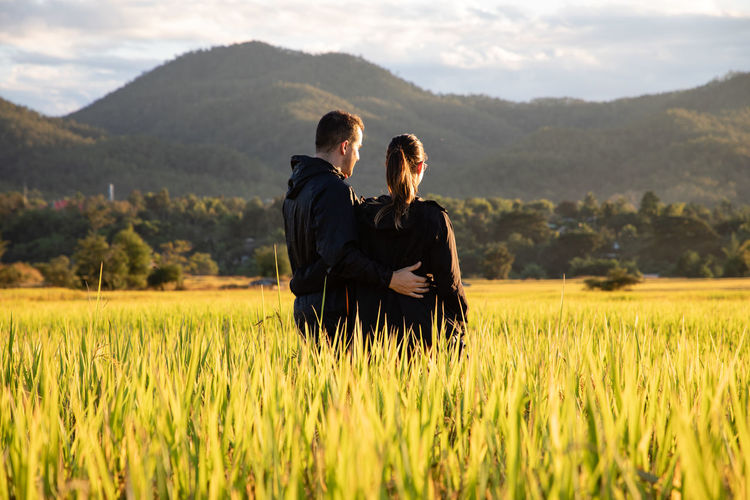 Couple standing at farm against mountains
