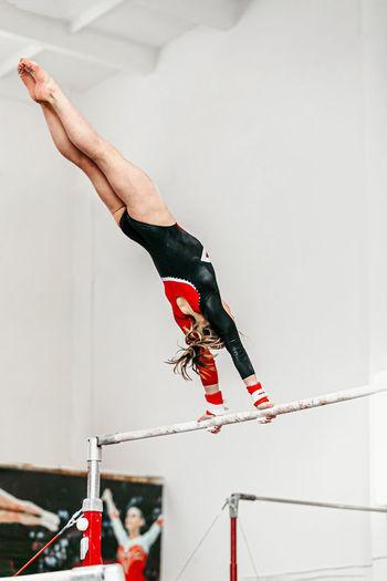 Woman performing gymnastic on bar