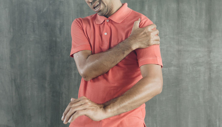 Midsection of man holding red while standing against wall