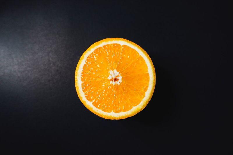 Close-up of orange slice against black background