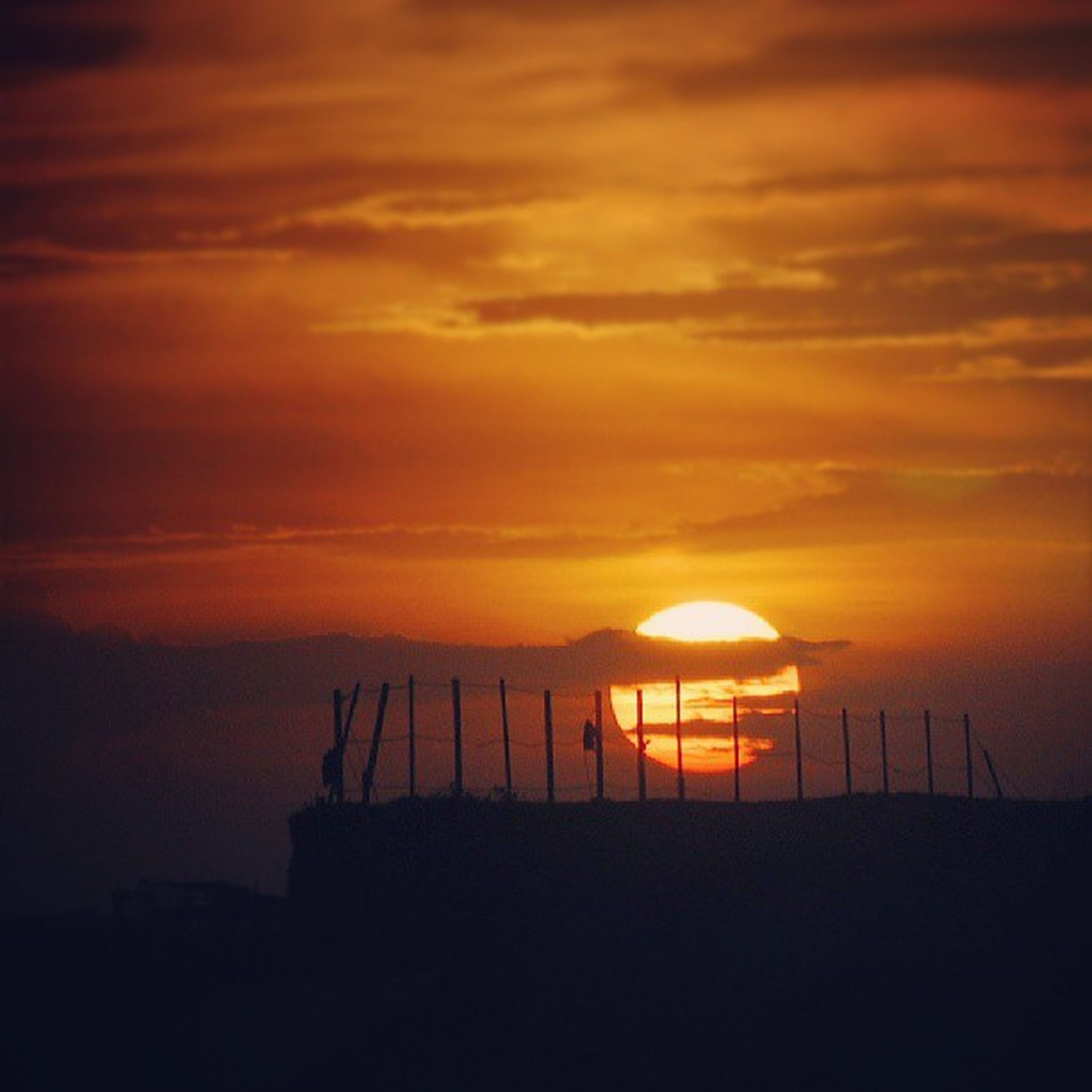 sunset, orange color, sky, silhouette, scenics, tranquility, tranquil scene, beauty in nature, cloud - sky, idyllic, nature, sea, sun, built structure, dramatic sky, railing, outdoors, architecture, no people, fence