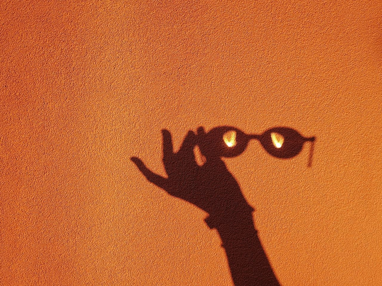 Shadow of hand holding sunglasses on orange wall during sunny day