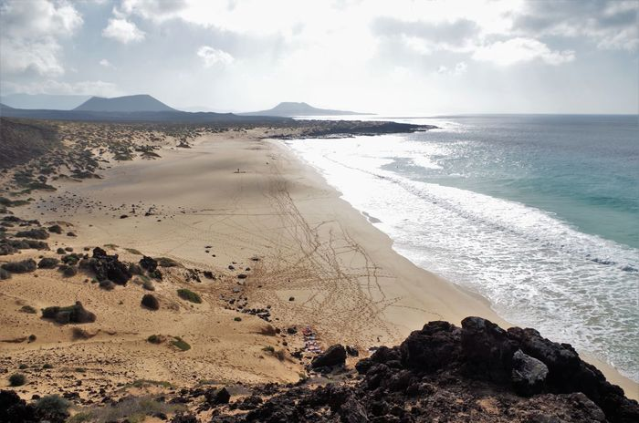 Playa de Las Conchas in the north of La graciosa, a small island north of lanzarote belonging to the canary islands in the atlantic. Atlantic Ocean Beach Beauty In Nature Canary Islands Cloud - Sky Day Horizon Over Water La Graciosa Landscape Lanzarote Mountain Nature No People Outdoors Playa De Las Conchas Sand Sand Dune Scenics Sea Sky Tranquil Scene Vacations Volcanic Landscape Volcanoes Water