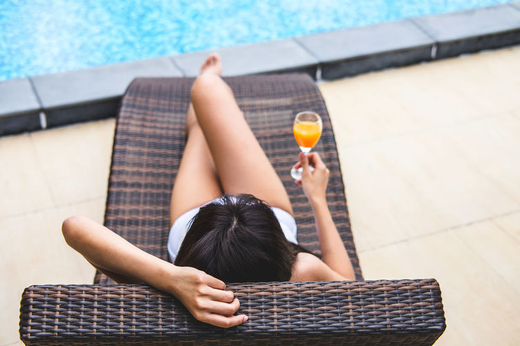 Woman having juice at poolside
