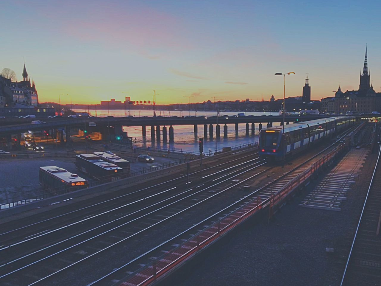 transportation, sky, track, architecture, rail transportation, mode of transportation, railroad track, built structure, sunset, water, nautical vessel, nature, building exterior, public transportation, high angle view, city, river, travel, no people, outdoors