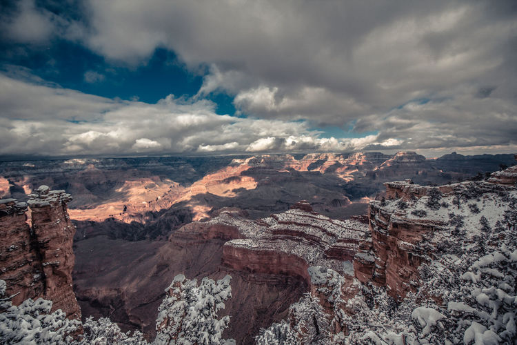 Aerial view of winter canyon landscape against cloudy sky