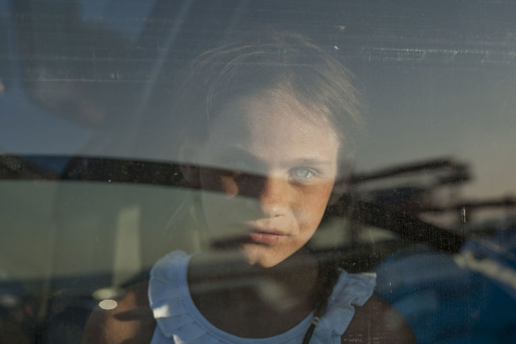 Portrait of girl seen through glass window