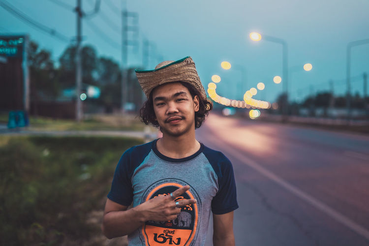 Portrait of young man standing on street in city at dusk