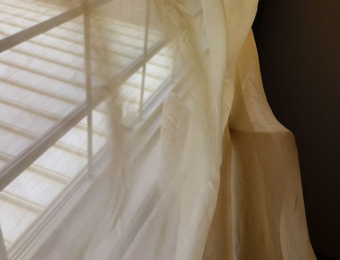 Close-up of white curtain hanging window