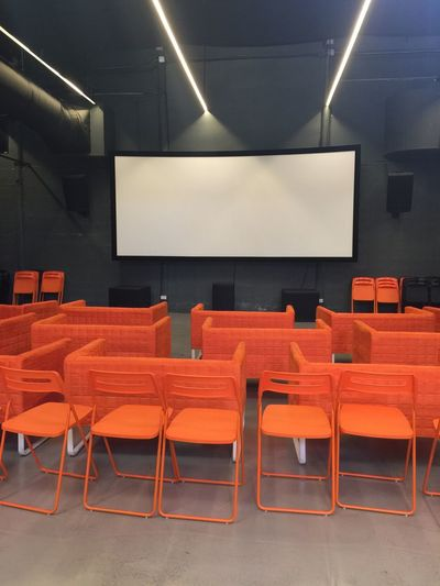 Presentation room with Orange chairs and White smart screen Performance Speaker Seminar White Orange Smart Screen Public Speaking Consulting MOVIE Speech Theater Audience Room Meeting Presentation Chair In A Row Empty Seat Indoors  No People Illuminated Film Industry Projection Equipment